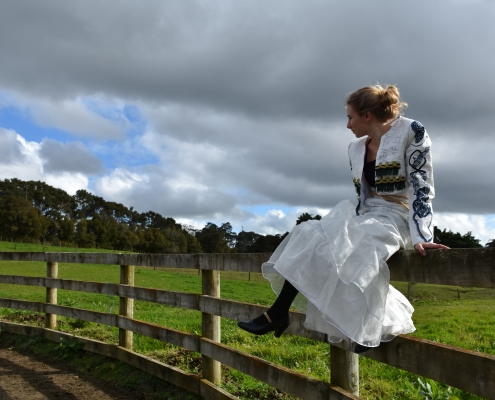 Chantelle Reilly sits on a wooden post and rail fence, modelling her Flamenco dress made of Luisetti Seeds sacks
