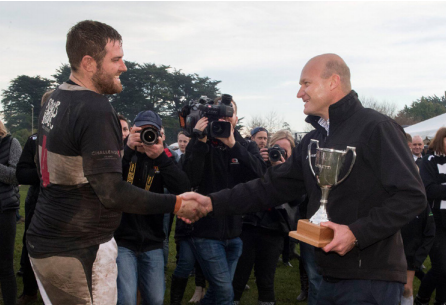 Edward Luisetti, presents the Luisetti Seeds Combined Country Cup to Waihora Captain; Matthew Stone. Matthew's clothes are muddy but he is smiling widely. In the background are a crowd of rugby fans.