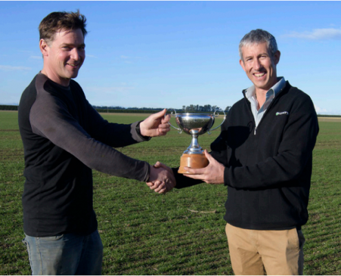 Left: Jan Lepoutre accepting a trophy with one hand and shaking hands with the other. Right: Jono Young hands over a trophy with one hand and shakes hands with the other. They are both standing in a lush green field, with blue sky behind them.