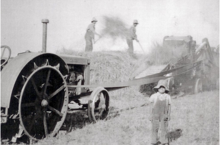 Image of a young David Morrish 1940 standing in front of a threshing machine. Two men in the background are blurred with movement
