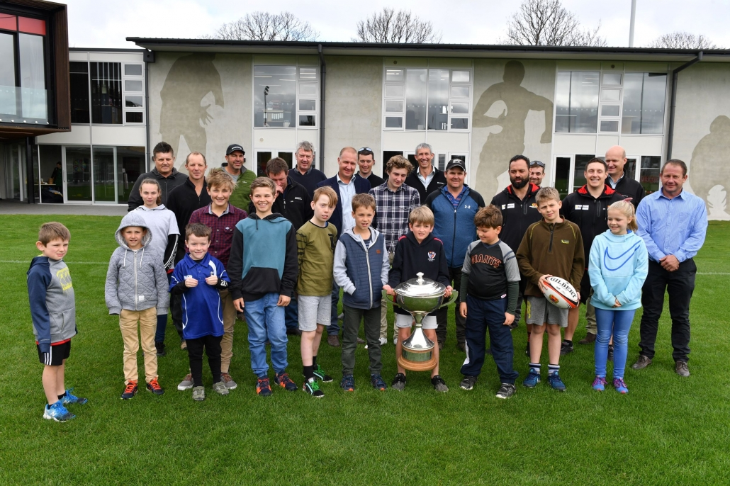 Group photo of 12 children and their parents gathered around the Mitre 10 Cup. In the crowd are Luisetti directors Edward and Vincent Luisetti. Canterbury Coach, Joe Maddock, and Canterbury Strength & Conditioning Coach, Gareth Duder.