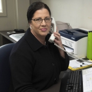 Image of Karen van Staden at her desk in reception. One hand rests on her keyboard while the other holds the phone to her ear. She is smiling, wearing a smart jacket and glasses.