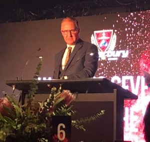 Vincent announces the Canterbury Rugby Women's Sevens Player of the Year at the 2018 Canterbury Rugby Awards. He stands at a podium. Behind him is a screen showing Rebecca's name, the crfu logo and fireworks