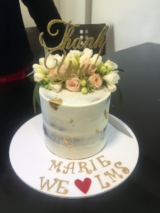 "A tall white cake topped with pink and white roses, with gold leaf details and a scrolling 'Thank You' in cursive as a topper. In icing below, ""Marie we heart LMS"""